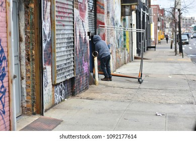 Brooklyn, New York, United States - February 22, 2018: Blue collar worker pulling hanger trolley in rougher looking street of Brooklyn.