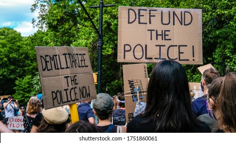 Brooklyn, New York / USA - June 7, 2020: People in a family protest march in Brooklyn holding signs that say Defund and Demilitarize the Police