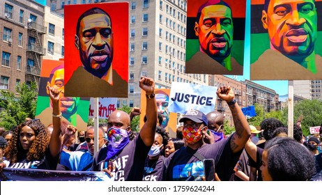 Brooklyn, New York / USA - June 19, 2020: Marchers raise their fists at a justice rally for George Floyd and celebration of Juneteenth