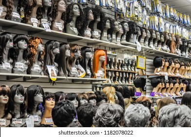 Brooklyn, New York / USA - May 4, 2012: An orange wig breaks the pattern of brunette and gray wigs in a wig shop.