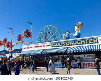 BROOKLYN, NY - APRIL 22, 2018: People pass by the famous Paul's Daughter fast food store in Brighton Beach Promenade near the Deno's Wonder Wheel Amusement Park.