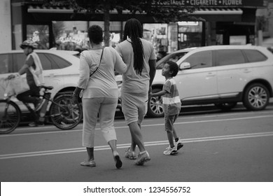 Brooklyn, NY; Aug 2018: A family walks hand in hand as they cross the street in Black and White