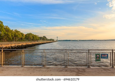 BROOKLYN, NY (August 10, 2017) - Midday at Pier 69 in Bay Ridge with the view of the Belt Parkway and the Verrazano Bridge in the background under a blue, orange sky.