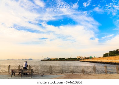 BROOKLYN, NY (August 10, 2017) - Midday at Pier 69 in Bay Ridge, with the view of Manhattan and Jersey City in the background under a blue, orange sky, fisherman preparing in the foreground.
