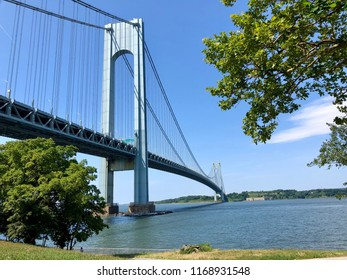 BROOKLYN, NY - July, 14, 2018: View on the Narrows and Verrazano  bridge from the Brooklyn waterfront side on a sunny day.