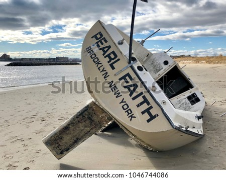 BROOKLYN, NY - MARCH 4, 2018: Overturned boat washed ashore by strong storm on Plumb Beach, Brooklyn, NY.