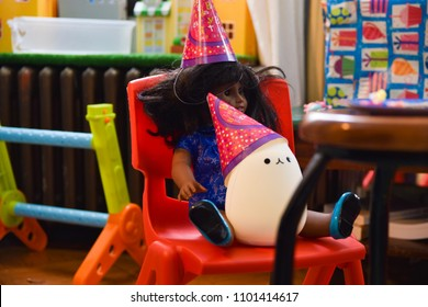 Brooklyn, NY - May 22, 2018: Two toys —Melody the civil rights marcher American Girl doll and Pusheen the cartoon cat — take a seat as guests at a child's birthday party.