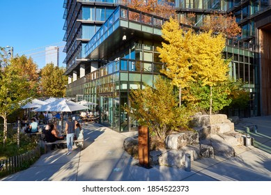 Brooklyn, NY - November 8 2020: Groups of people sit at tables outside at the Osprey Restaurant in Brooklyn Bridge Park on a sunny autumn day. The restaurant is located in 1 Hotel Brooklyn Bridge.