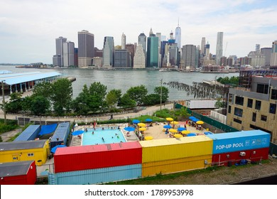Brooklyn, NY / USA - July 15, 2016: Panoramic View of Manhattan and A Colorful Pop-up Swimming Pool in Brooklyn Bridge Park.