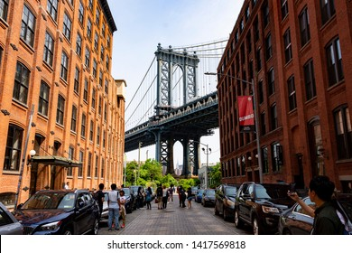 Brooklyn, NYC, New York, United States - June 2, 2019: Tourists and passersby on Washington St in DUMBO neighborhood of Brooklyn taking pictures and seflies of the Manhattan Bridge.