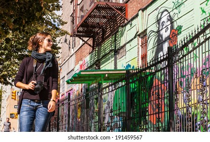 BROOKLYN, NYC, US, September 29 2013: Street art in Williamsburg, Brooklyn. Female photographer with sunglasses walking next to a wall of graffiti in Brooklyn, New York, US.