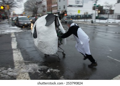 BROOKLYN, NY/USA - JANUARY 24 2015: Teams of costumed participants push shopping carts through snow covered Brooklyn streets as part of Idiotarod NYC XI.