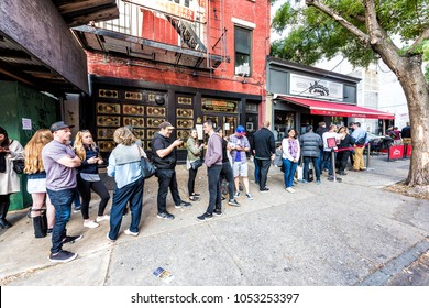 Brooklyn, USA - October 28, 2017: Long line queue of people crowd waiting for famous restaurant food called Juliana's Pizza