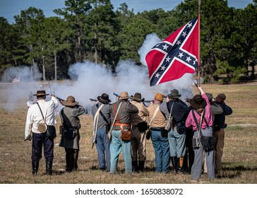 Brooksville, FL - January 18, 2020: Confederate battle flag flies over a group of civil war reenactors as they fire on the enemy.