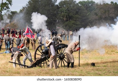 Brooksville, FL - January 19, 2020: Civil War reenactors fire a large canon, with a confederate flag in the background, at an event in Brooksville, FL.