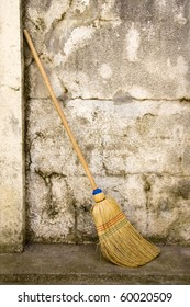broom against a rough wall