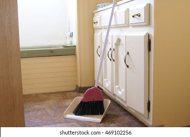A broom and a dust pan on the floor in a quaint small bathroom. Apartment cleaning, everyday, small space living.
