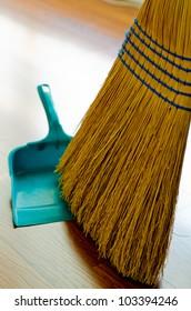 Broom and dust pan on hardwood floor.