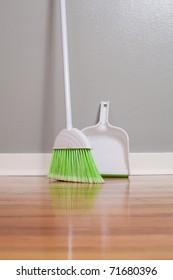 A broom and dust pan on New Hardwood Flooring