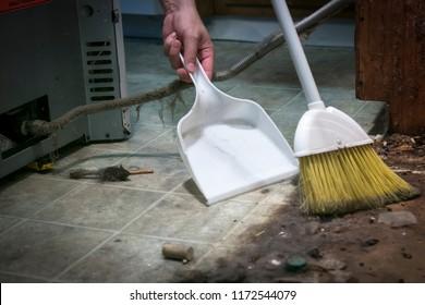 Balais et poêle balayant la saleté et les débris de sous-appareils de cuisine.