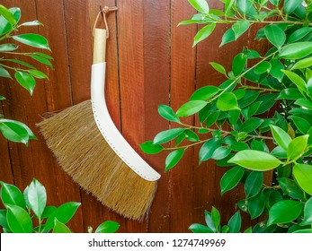 broom hanging on the wooden wall ready for cleaning stockphoto