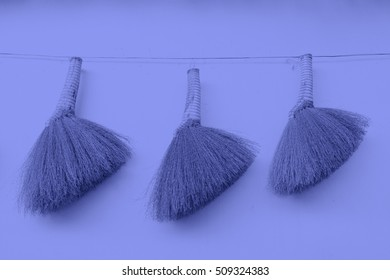 Broom hung on the white wall, closeup of photo