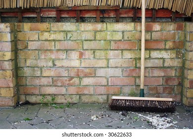 Broom leaning against wall ready to sweep litter.