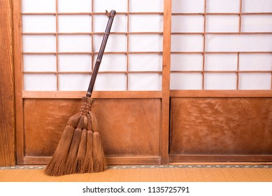 Broom made from chusan palm which lean on paper sliding door