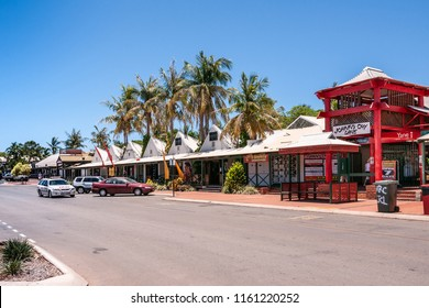 Broome, WA, Australia - November 29, 2009: Street view with cars and people in front of white and red Johnny Chi Lane shopping mall with palm trees and blue sky.