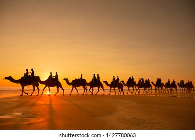 Broome, Western Australia, Australia ; 05 August 2017: Tourists taking a Camel ride along Cable Beach for sunset