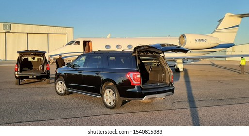 Broomfield, Colorado - October 24, 2019: Luxury SUVs parked by a private jet
