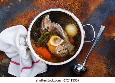 Broth soup in a cooking pot with ladle on dark stone background. Top view