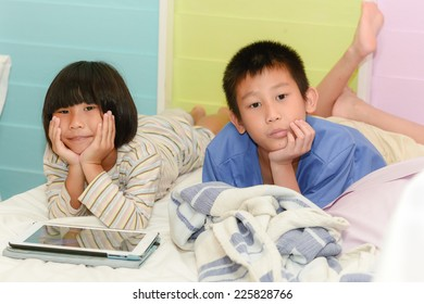 Brother ans sister siblings together on bed using tablet