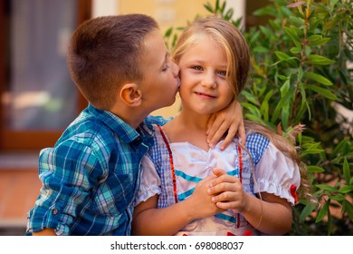 Brother boy are kissing his sister girl on the cheek, warm hugs in nature outside near the house. she smiles happy. Brother and Sister Elementary Childhood Kid Playful Concept