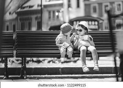 brother feeding sister with ice cream sitting on bench