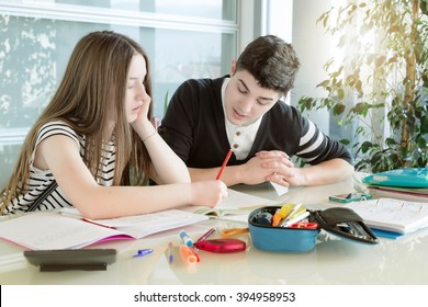 Brother helps her sister to do their homework