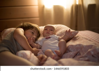 Brother and his baby sister lying in bed in the morning. Image with selective focus and toning.