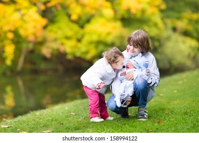 Brother and his little toddler sister comforting and kissing their newborn crying baby brother on a walk in a beautiful autumn park
