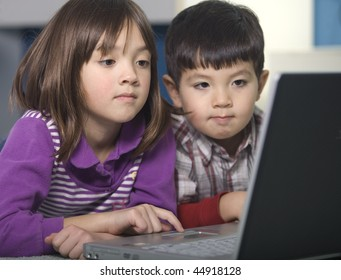 A brother and his older sister use the laptop.