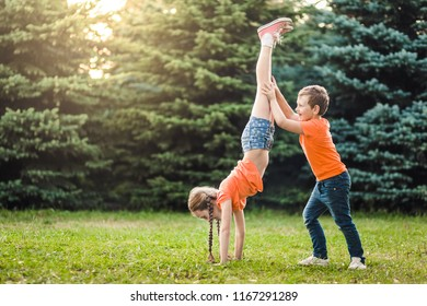 Brother holding his sisters' legs while she is staying on her arms on grass on spruce fir background