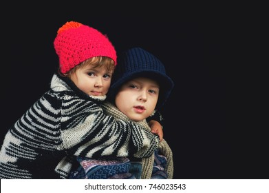Brother hugging sister on a dark background .The children are dressed in warm sweaters and caps .
