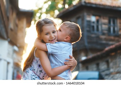 brother kissing smiling sister in sunny street