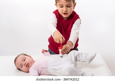 Brother paying as doctor and patient with his baby sister. The boy makes injection with syringe.