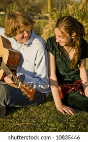 A brother plays guitar and sings with his younger sister.