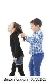 Brother pulling sister's hair. Isolated on white background