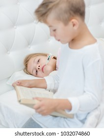 brother reads the book to the sick sister