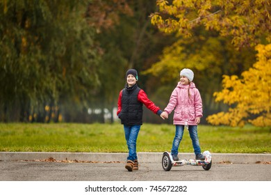 The brother rolls his younger sister on gyroscope in the autumn park.