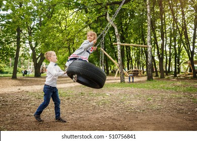 The brother rolls the younger sister on a tire swing. Children playing outdoors in summer.