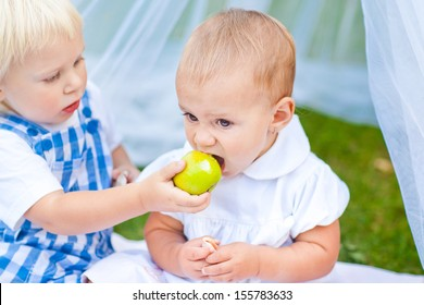 Brother share an apple with her sister.