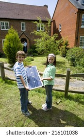 Brother and sister (6-10) with solar panel by house, portrait